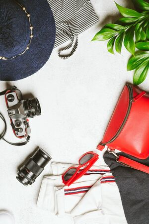 Set of women's clothing and accessories for summer holidays travel in red, blue and white colors. Travel vacation concept. Summer background. Top view copy space. 版權商用圖片