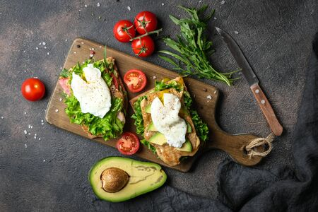 Delicious sandwich with avocado and poached egg on a dark background.  版權商用圖片
