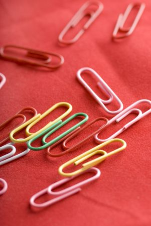 Color paper clips to background. Isolated on red background Stock Photo - 6822434