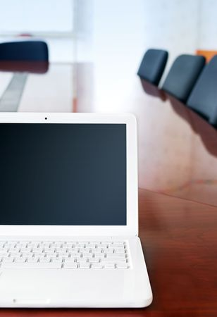 on the foreground: Laptop on table with chairs near by in office Stock Photo