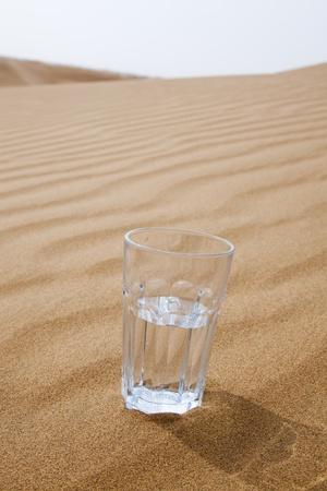 optimismo: Vaso de agua medio vacía en el desierto Foto de archivo