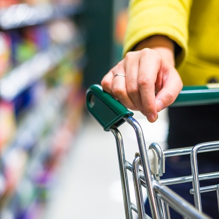 asian shopper: Closeup of female shopper with trolley at supermarket