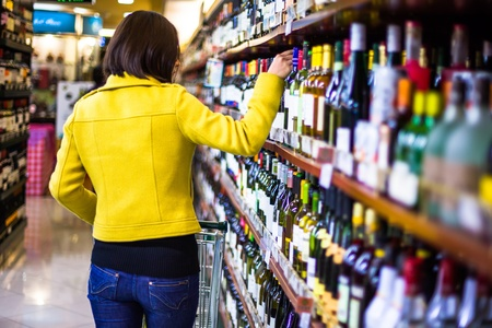 produce sections: Young woman shopping in the supermarket,wine shelves