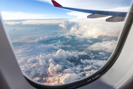 Wolken en de hemel gezien door het raam van een vliegtuig bij zonsondergang