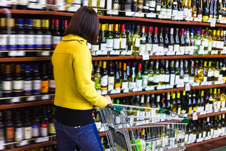 Young woman shopping in the supermarket,wine shelves
