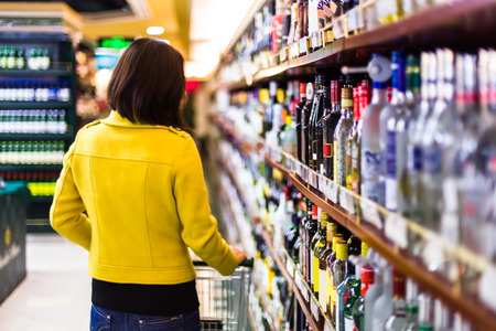 Young woman shopping in the supermarket,wine shelves photo