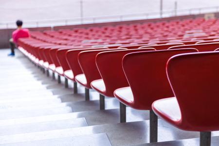 bleachers: Red chairs bleachers in large stadium Stock Photo