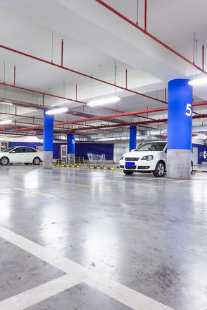 parking lot interior: Parking garage, underground interior with a few parked cars