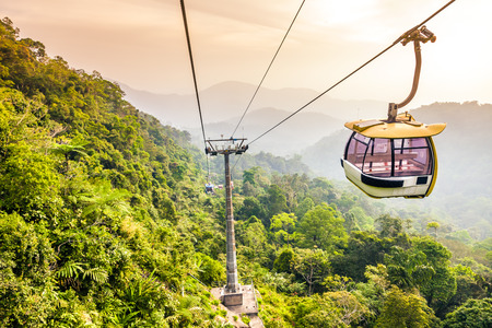Aerial tramway moving up in tropical jungle mountains photo