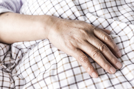 The patient's hand on the bed