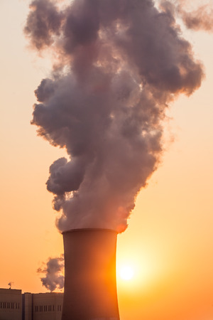 radiation pollution: chimney and cooling towers of power plant during sunset Stock Photo