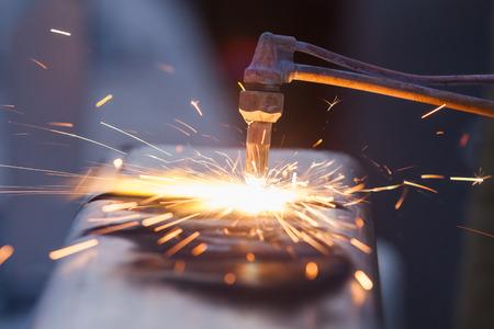 Ouvrier à la découpe de tuyaux en acier en utilisant la torche de métal et installer une clôture en bordure de route Banque d'images