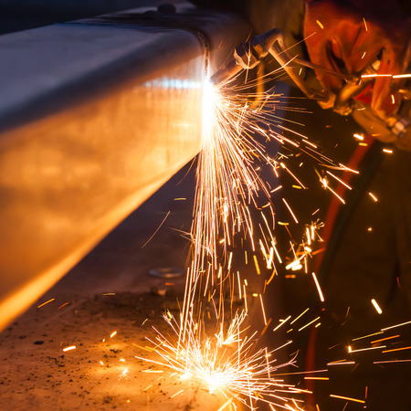 worker cutting steel pipe using metal torch and install roadside fence photo