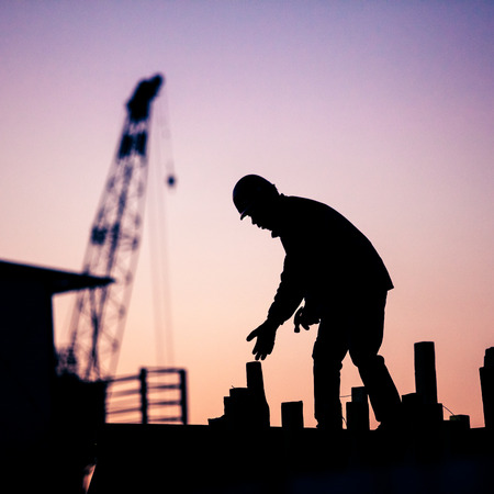 construction crane: silhouette of construction worker Stock Photo