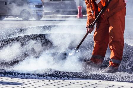 アスファルト道路装服でシャベルで作っている労働者 写真素材