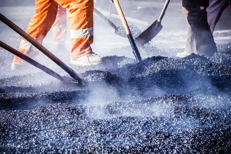 道路建設でシャベルでアスファルトを作る労働者