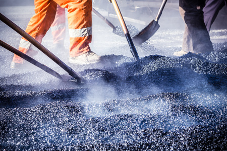 vibration machine: Workers making asphalt with shovels at road constructio