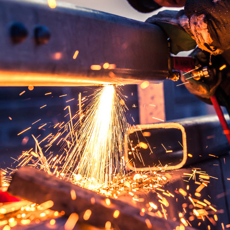 glass fence: worker cutting steel pipe using metal torch and install roadside fence