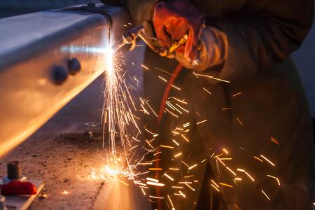 siderurgia: el corte de tubos de acero que usa la antorcha de metal e instalar la cerca en carretera trabajador