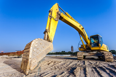 power shovel: Big excavator on new construction site Stock Photo