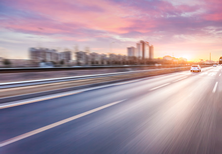 motion: Car driving on freeway at sunset, motion blur
