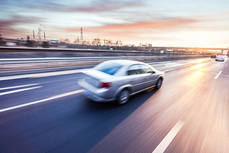 cars on the road: Car driving on freeway at sunset, motion blur