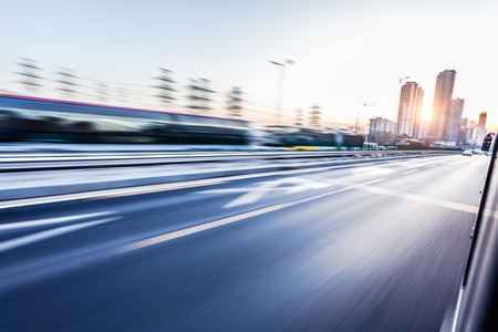 fast car: Car driving on freeway at sunset, motion blur