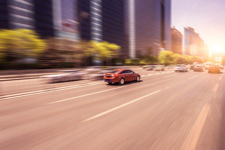 Car driving on road at sunset, motion blur Foto de archivo