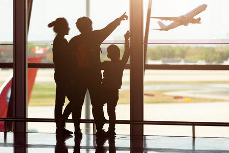 viaje familia: Silueta de joven familia en el aeropuerto