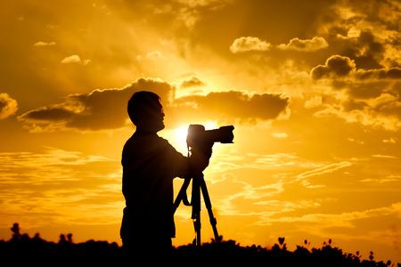 fotógrafo de tomar una foto en la puesta del sol