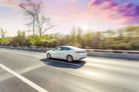 Car driving on road, motion blur Stockfoto