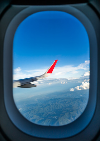 airplane wing: Clouds and sky as seen through window of an aircraft