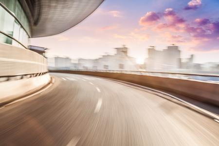 Jazdy samochodem na drodze w tle miasta, motion blur