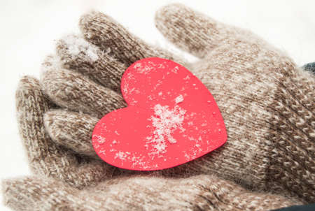 Womens hands in knitted warm wool gloves hold a red heart, against the background of snow, in winter, Valentines day concept, close-up