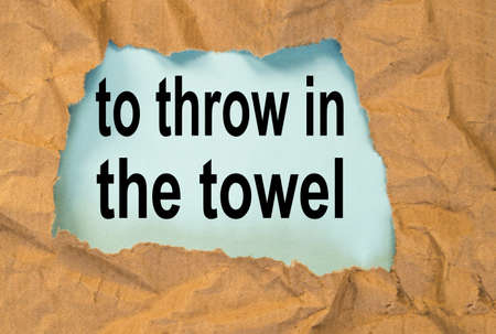 throw in the towel-phrase message through a hole in the crumpled wrapping paper, conceptual image, top view