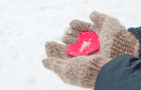 Womens hands in knitted warm wool gloves hold a red heart, against the background of snow, in winter, Valentines day concept