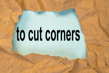 to cut corners-a message through a hole in crumpled wrapping paper, a conceptual image, a top view Banque d'images