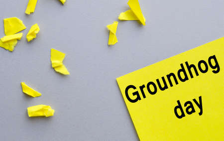Groundhog day, written on yellow paper, lying on a gray background, scattered around torn small pieces