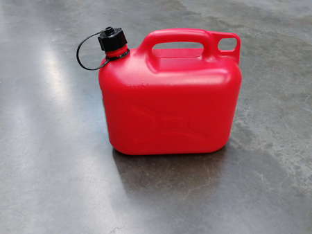 Red plastic canister for flammable liquids with black lid on the concrete