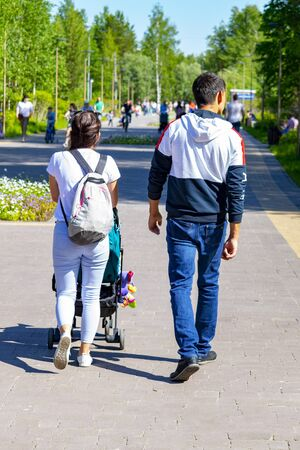A woman and man are walking along a path in the park. A woman rolls a childs carriage. Rear view, Surgut, Russia - June 30, 2019