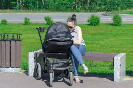 A young mother sits on a pram. Front view, Surgut, Russia - June 30, 2019 Editöryel