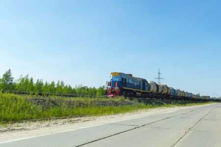 A blue locomotive tows a fuel tanks wagons against a blue sky. Side view