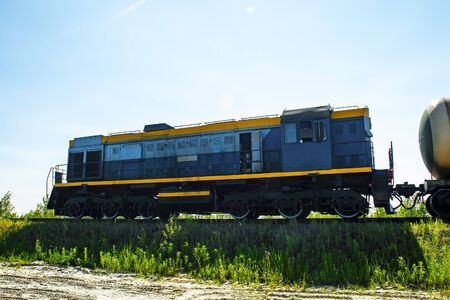 locomotive tows fuel tank wagon against blue sky. Side view