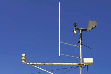 Weather station weather station and other measuring devices against a blue sky. Front view