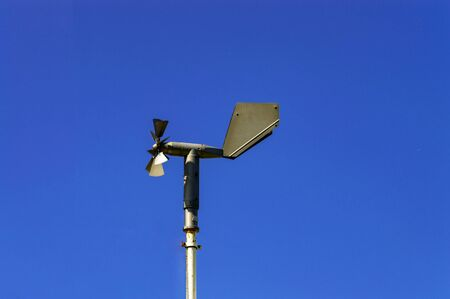 Weathervane weather station with a propeller against a blue sky. Front view