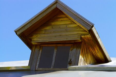 Attic roof window of an old wooden house. View from below.