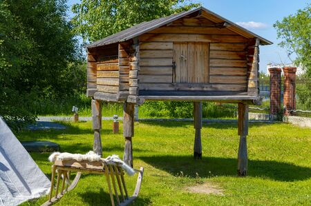 Wooden log warehouse on the logs-legs of the indigenous peoples of Siberia. Front view.