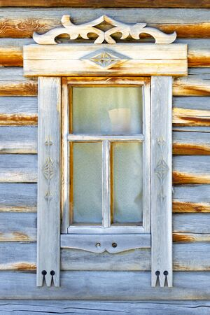 Window in a wooden log house. Front view.