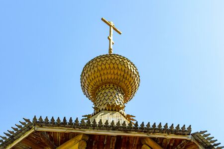 Dome with a cross of a wooden Christian church in the sun. View from below.