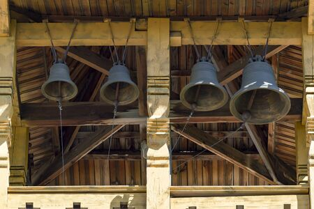 Bells and bell tower in an old wooden christian temple. Front view Stok Fotoğraf